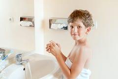 Мальчик моет руки Стоковая Фотография