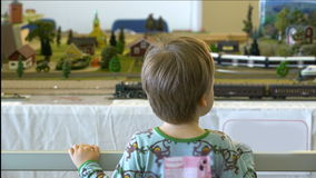 Мальчик наблюдая совершенные модели поездов и железнодорожного вокзала сток-видео