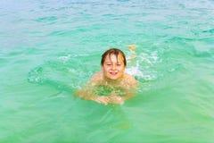 Мальчик наслаждается поплавать в океане стоковые изображения rf