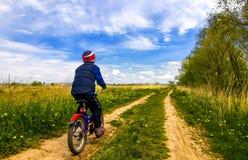 Мальчик на велосипеде на проселочной дороге в солнечном дне Стоковая Фотография RF