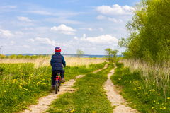 Мальчик на велосипеде на проселочной дороге в солнечном дне Стоковые Изображения RF