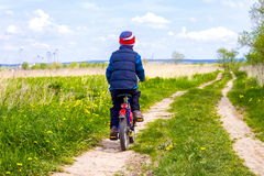 Мальчик на велосипеде на проселочной дороге в солнечном дне Стоковое Изображение