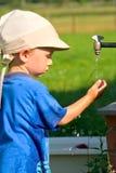 Мальчик на воде из крана стоковое изображение