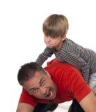 Мальчик на его отцах подпирает, воспитание может быть diffic Стоковые Фотографии RF