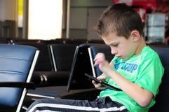 Мальчик на его таблетке на авиапорте Стоковые Изображения