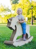 Мальчик на единороге игрушки Травянистое поле на парке field вал усмехаться мальчика и he& x27; s счастливый Стоковая Фотография RF