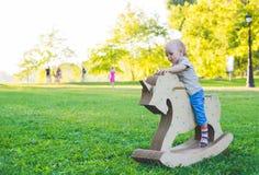 Мальчик на единороге игрушки Травянистое поле на парке field вал усмехаться мальчика и he& x27; s счастливый Стоковое фото RF
