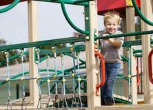 Мальчик на оборудовании спортивной площадки. Стоковые Изображения RF
