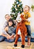 Мальчик на лошади игрушки с его родителями под деревом Chrismas Стоковая Фотография