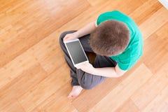 Мальчик на поле держа таблетку в взгляде высокого угла Стоковая Фотография