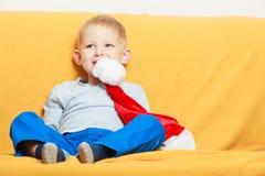 Мальчик на софе держа шляпу рождества Стоковое Изображение RF