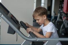 Мальчик на третбане на спортзале Стоковое Изображение