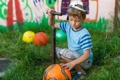 Мальчик надувает насос футбольного мяча Стоковая Фотография RF