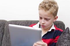 Мальчик на ipad Стоковое Изображение