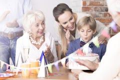 Мальчик дня рождения семьи наблюдая стоковые изображения rf