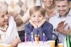 Мальчик дня рождения смотря торт стоковое фото rf