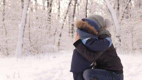 Мальчик обнимая его мать в снежном парке в зиме видеоматериал