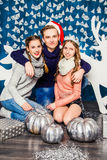 Мальчик обнимая 2 красивых девушек на предпосылке рождества d Стоковое Изображение RF