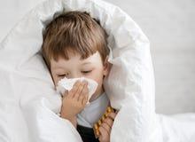 Мальчик обтирает его нос с тканью стоковые фотографии rf