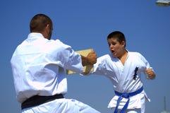 Мальчик ломая доску в практике боевых искусств Стоковые Фото