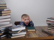 Мальчик достигает для стога книг Стоковая Фотография RF