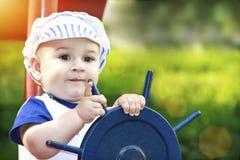 Мальчик одевал как матрос держа рулевое колесо стоковое фото