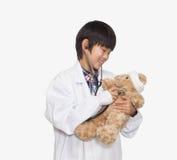 Мальчик одевал как доктор проверяя показатели жизненно важных функций плюшевого медвежонка, съемку студии Стоковое Фото