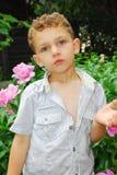 Мальчик пахнуть пионом. Стоковая Фотография