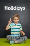 Мальчик перед школьным правлением с ПРАЗДНИКАМИ текста Стоковые Изображения