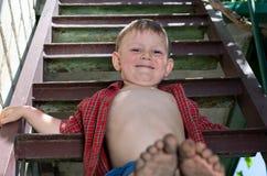 Мальчик показывая его пакостные ноги Стоковая Фотография RF
