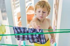 Мальчик помогает ее матери повиснуть вверх одевает стоковая фотография rf