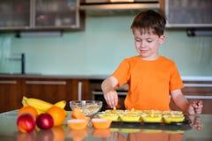 Мальчик помогая с печеньями выпечки стоковые изображения