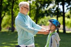 Мальчик порции старика с шлемом велосипеда на парке Стоковое Фото