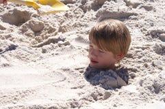 Мальчик похороненный в песке Стоковые Изображения
