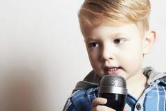 Мальчик поя в microphone.child в karaoke.music Стоковые Изображения
