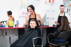 Мальчик положительных женских волос вырезывания парикмахера милый Стоковое Фото
