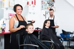 Мальчик положительных женских волос вырезывания парикмахера усмехаясь Стоковые Изображения RF