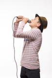 Мальчик подростка брюнет певицы в розовом jersey в шляпе золота с микрофоном Стоковые Фотографии RF