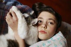 Мальчик подростка в кровати с cullde кота Стоковое Изображение RF