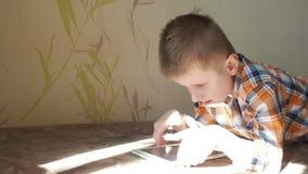 Мальчик подростка используя сенсорную панель лежа в кровати сток-видео