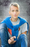 Мальчик подростка сидя на крупном плане стены Стоковые Фотографии RF