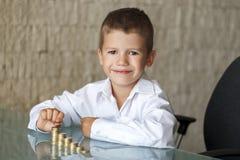 Мальчик подсчитывая монетки одного евро в офисе Стоковые Фотографии RF