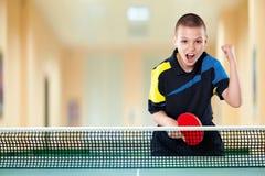 Мальчик празднуя безупречную победу в настольном теннисе стоковые фотографии rf