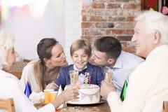 Мальчик празднуя день рождения с семьей стоковое изображение