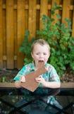 Мальчик принимая укус из зайчика шоколада Стоковая Фотография