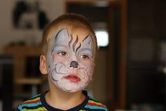 Мальчик при голубая бабочка покрашенная на его стороне Стоковые Изображения