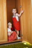 Мальчик при девушка играя прятк Стоковые Изображения