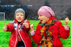 Мальчик при девушка смеясь над на заднем плане футбольного поля Стоковое Фото