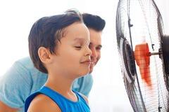 Мальчик при его папа охлаждая перед вентилятором стоковая фотография rf
