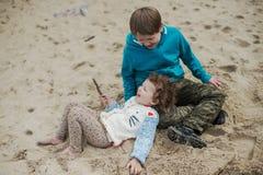 Мальчик при его сестра играя на пляже Стоковое фото RF